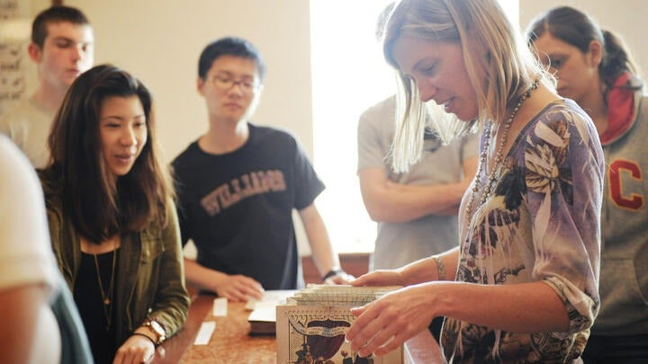 An instructor shows students an item from Special Collections.