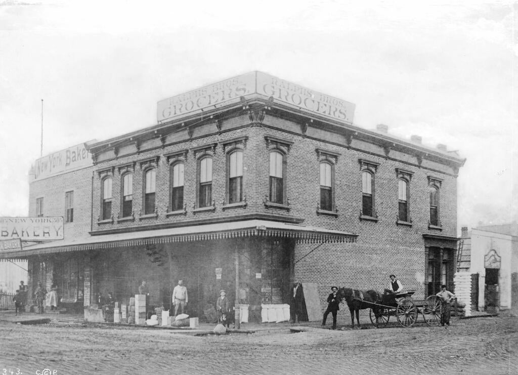 Exterior view of Ralphs Brothers Grocery and New York Bakery, located on the southwest corner of Sixth Street and Spring Street, 1886. Part of the California Historical Society Collection in the USC Digital Library.